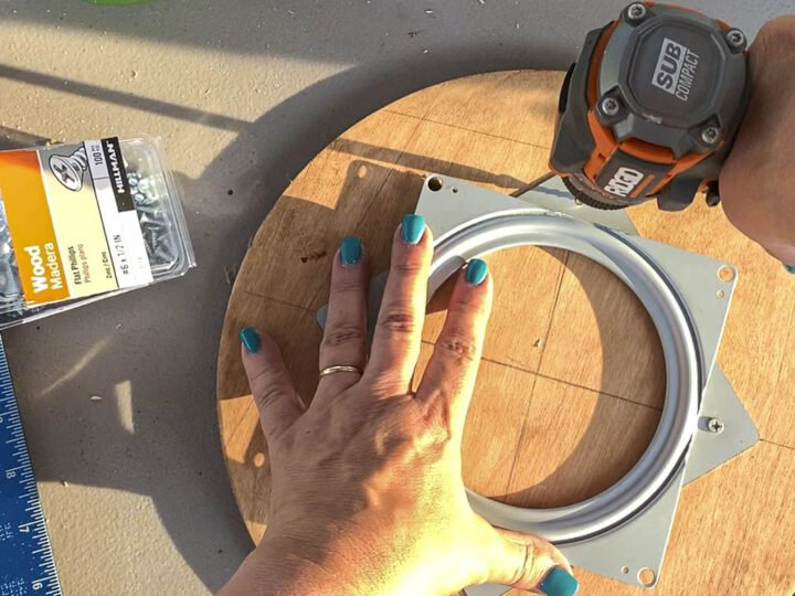 Attaching the Lazy Susan swivel plate to the top of the smaller base board using small screws.