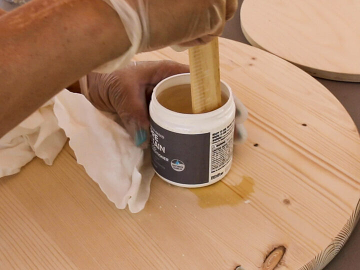 Mixing pre-stain wood conditioner with a painting stick.