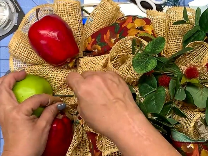 Hands attaching an artificial apple to a mesh wreath using floral picks.