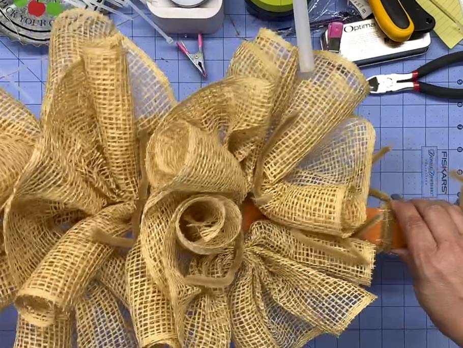 Poly burlap mesh ruffles attached to a painted yard stick with pipe cleaners.