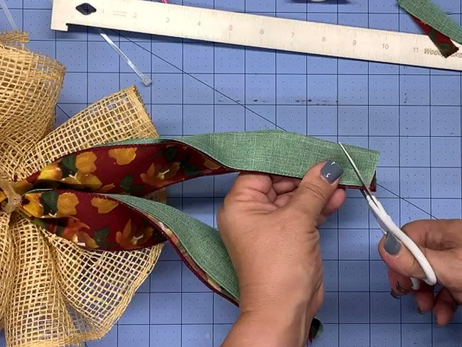 Cutting the end of folded ribbons at an angle to form a dovetail.