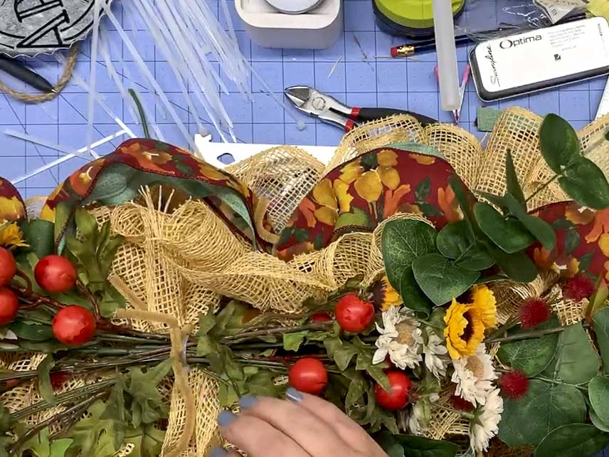 Using a pipe clear to attach greenery and flowers to a swag.