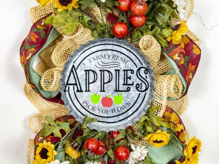 """A fall swag made of poly burlap mesh decorated with ribbons, apples and flowers in autumn colors. Features a round metal sign saying """"Farm Fresh Apples – Pick Your Own."""""""