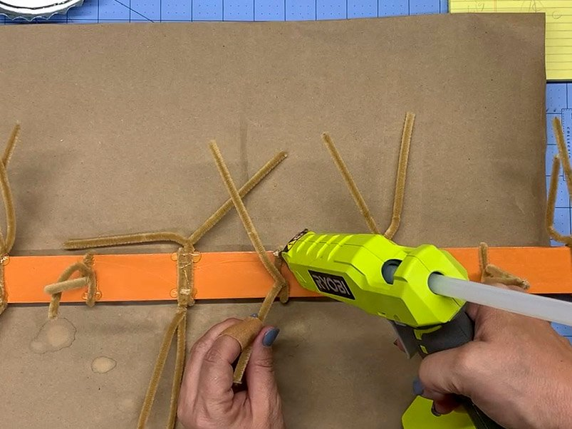 Using hot glue to attach pipe cleaners to a painted yard stick.
