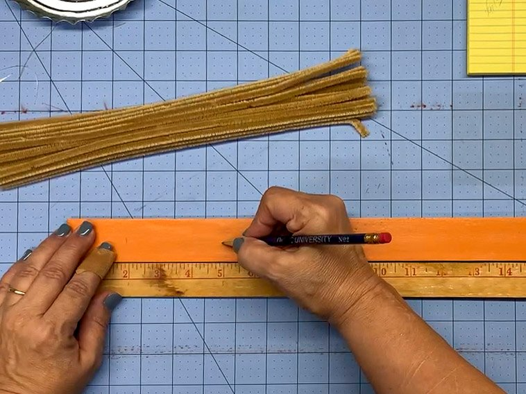 Hands marking a painted yardstick every 3 inches to indicate where to place pipe cleaners.