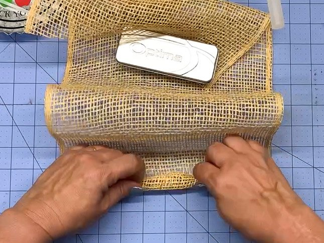 Hands rolling up one end of a strip of poly burlap mesh to make a woodland ruffle for the door swag.