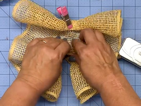 Hands scrunching up the length of a poly burlap mesh strip to make a woodland ruffle for an autumn door swag.
