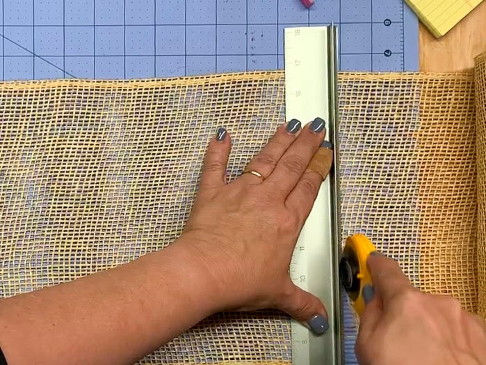 Hands holding a metal ruler and a rotary cutter to cut a piece of poly burlap mesh.