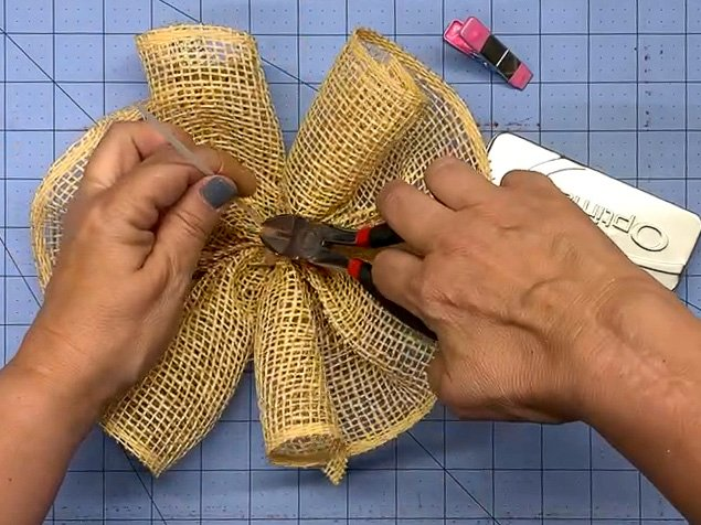 Hands using a wire cutter to trim the end of a zip tie on a mesh ruffle for a wreath.