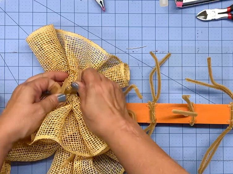 Hands twisting a pipe cleaner around a mesh ruffle to attach it to a wreath form.