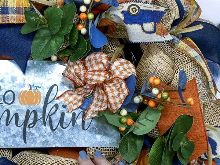 Mini swag made of artificial eucalyptus and autumn berries on a metal Hello Pumpkin wreath sign