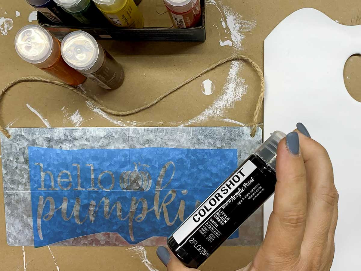 Hand holding a bottle of COLORSHOT premium acrylic paint over a stencil.