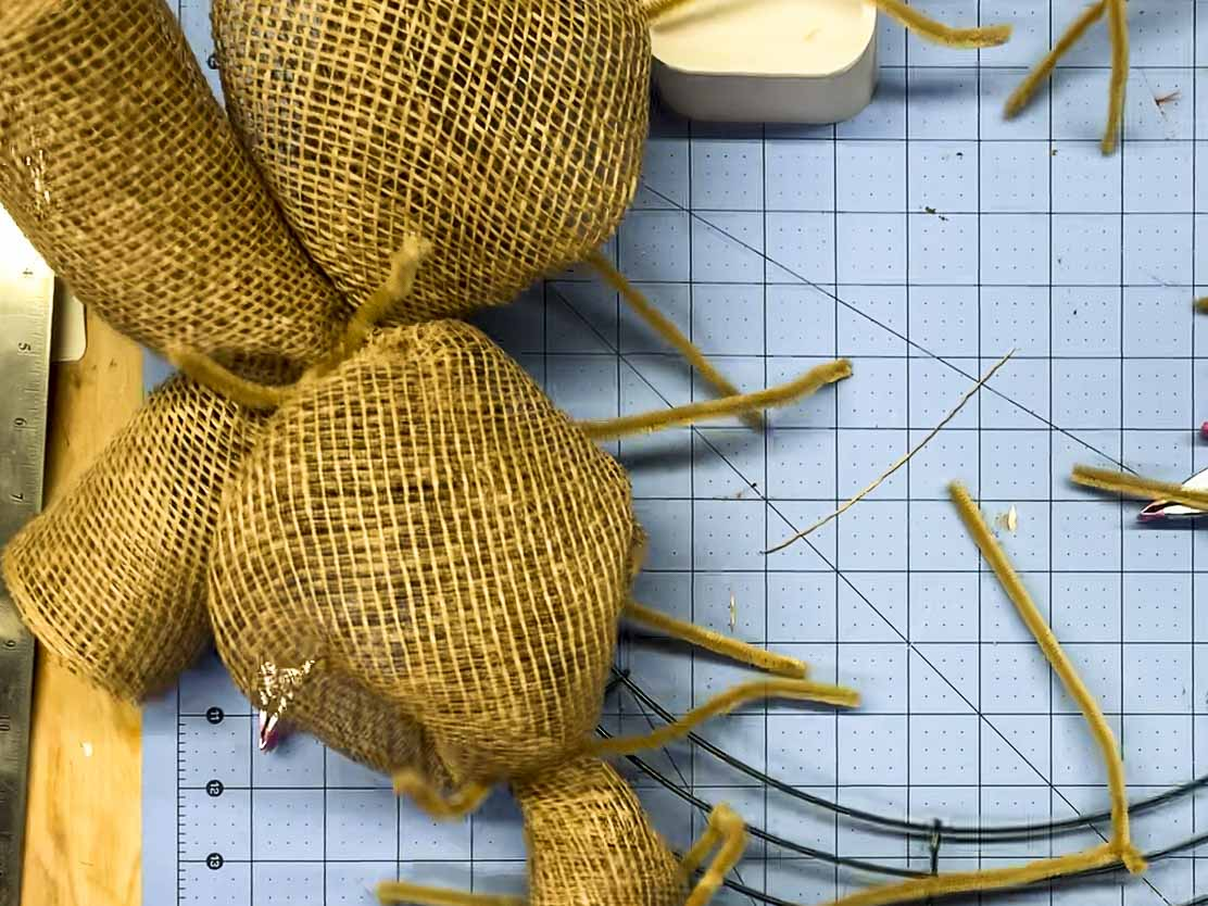 Pair of mesh curls crossed and attached to the same point on the wire wreath form using a single pipe cleaner