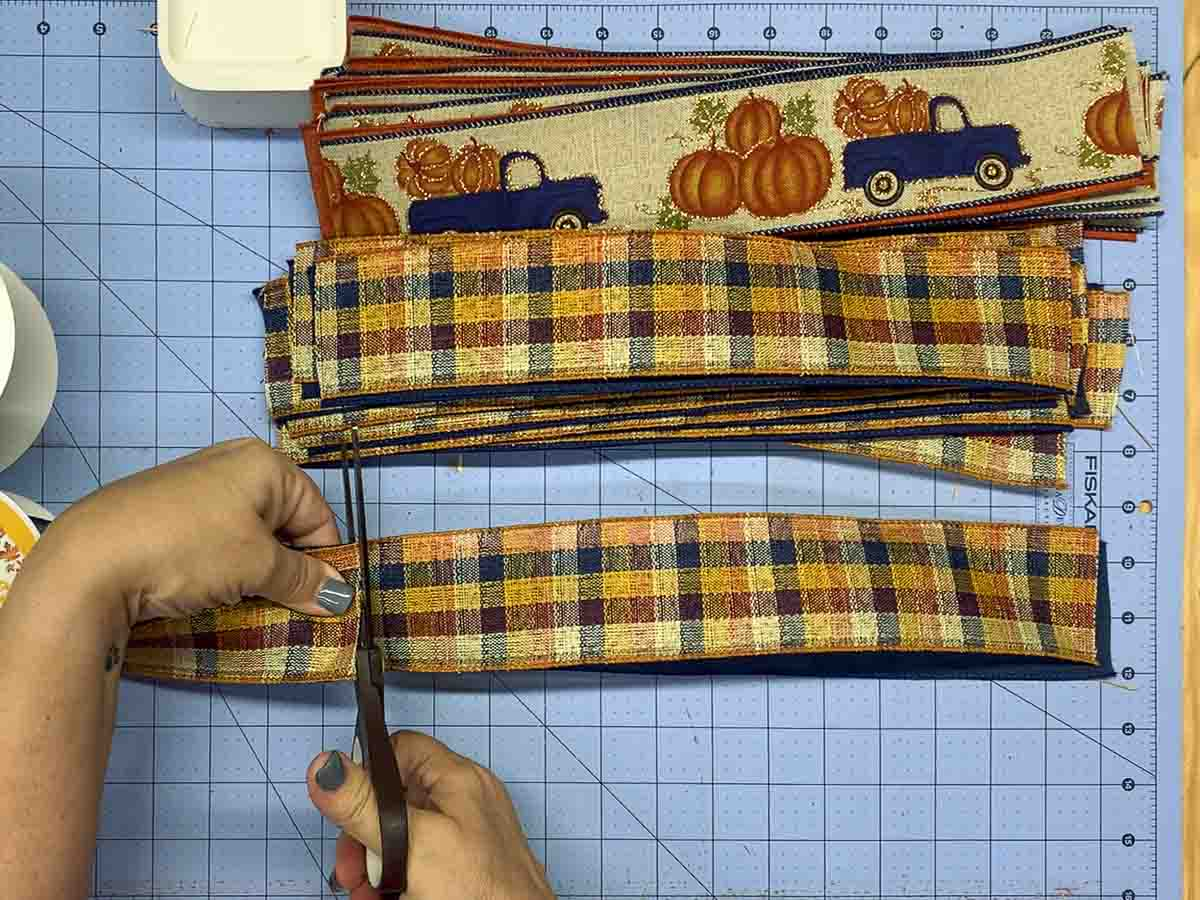"""Hands cutting 13"""" lengths of 2.5""""-wide ribbon."""