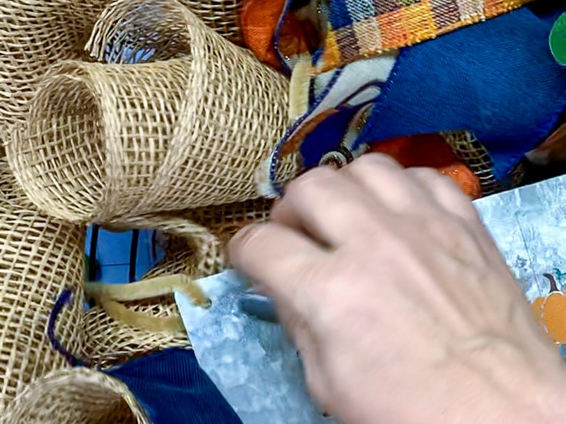 Using a pipe cleaner to attach a metal sign to a mesh pumpkin wreath