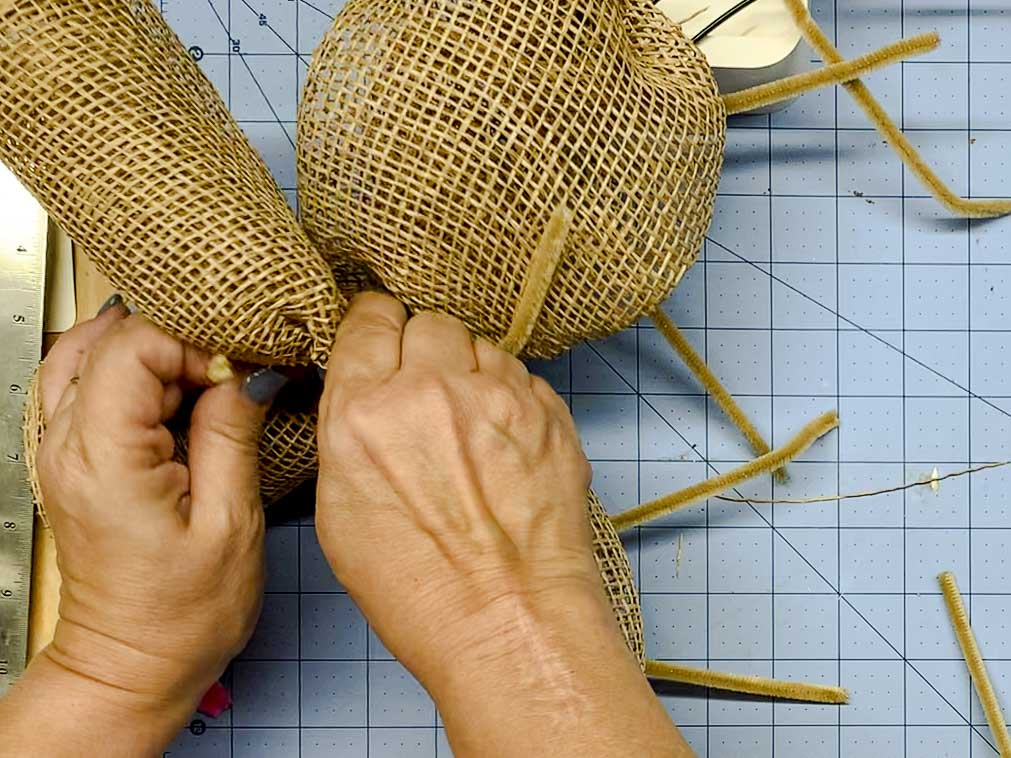 Hands attaching the second piece of mesh to the wreath form.