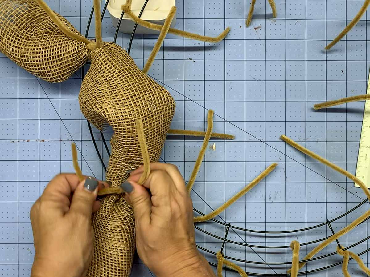 Hands attaching the other end of the rolled piece of mesh to the wire wreath frame using pipe cleaners.