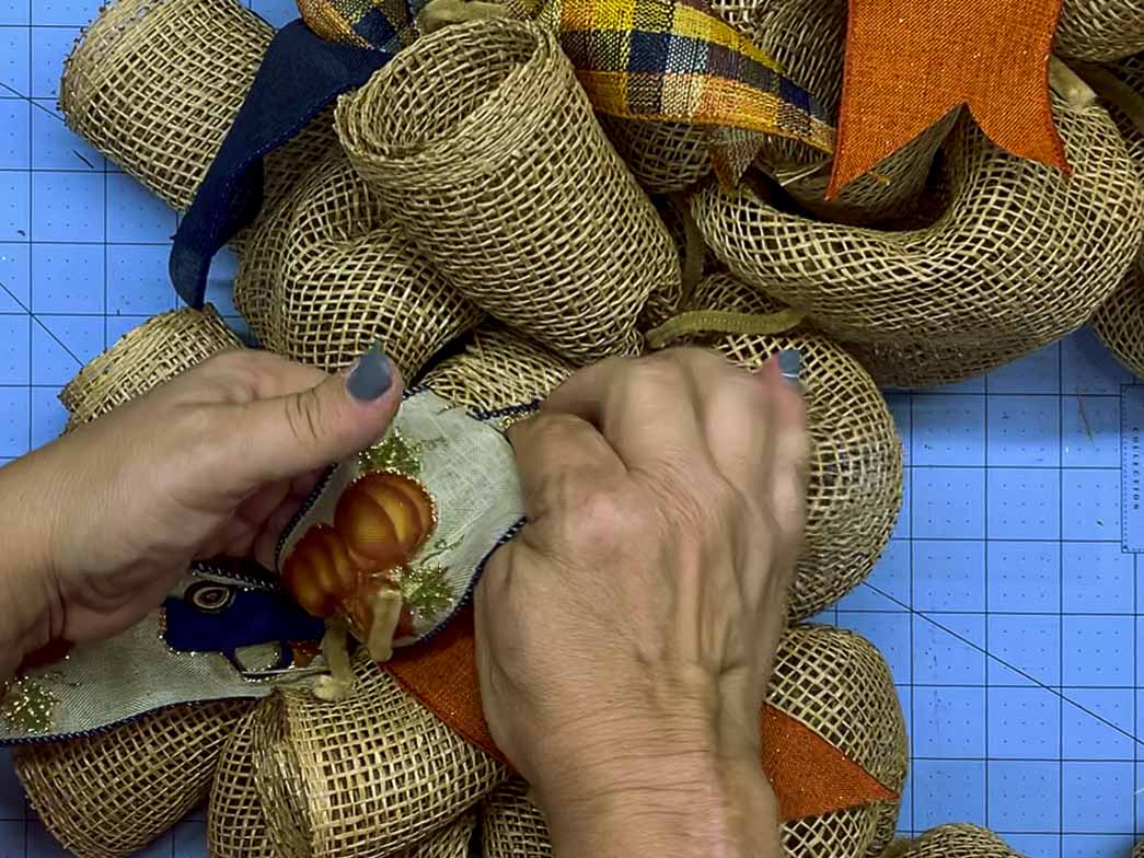 Hands curing the end of a pumpkin ribbon tail on a mesh wreath.