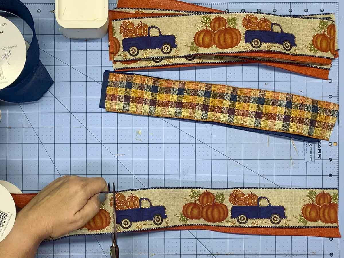 """Hand cutting 13"""" lengths of 2.5"""" wide ribbon. Ribbon has a print of blue pickup trucks with a bed of pumpkins."""