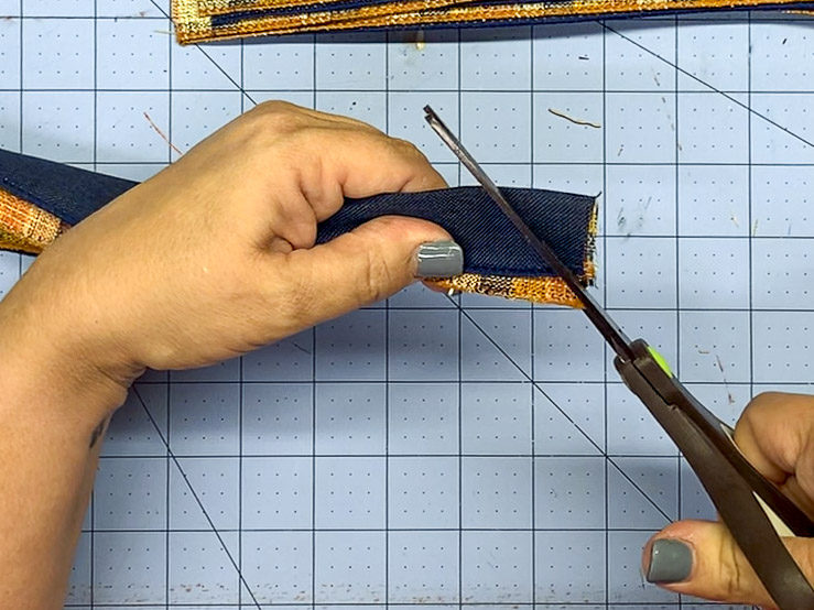 Cutting the end of a folded end of ribbon at an angle to create a dovetail.