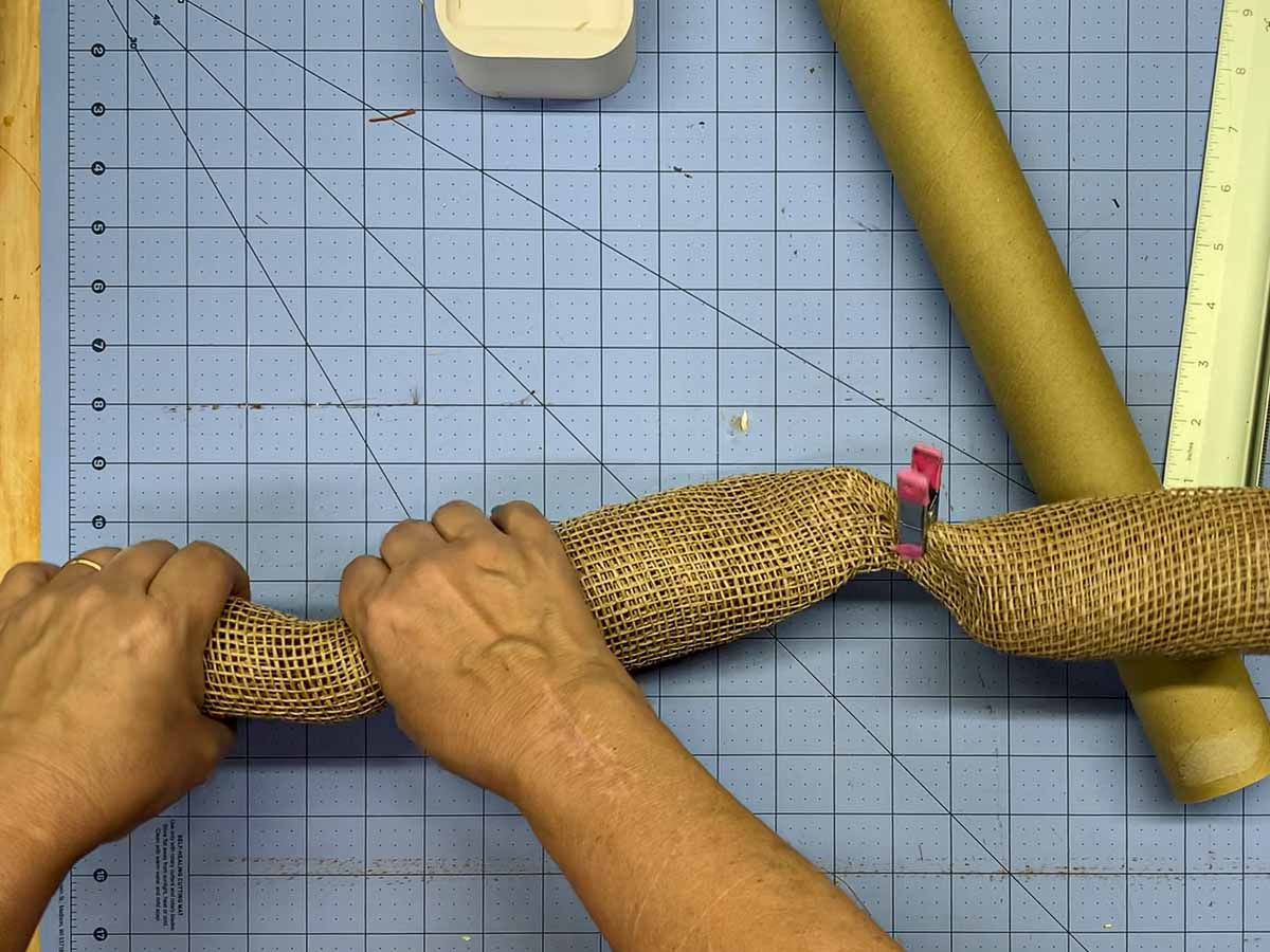 """Hands pinching 21"""" length of rolled burlap about 4"""" from the end to form a curl at the end."""