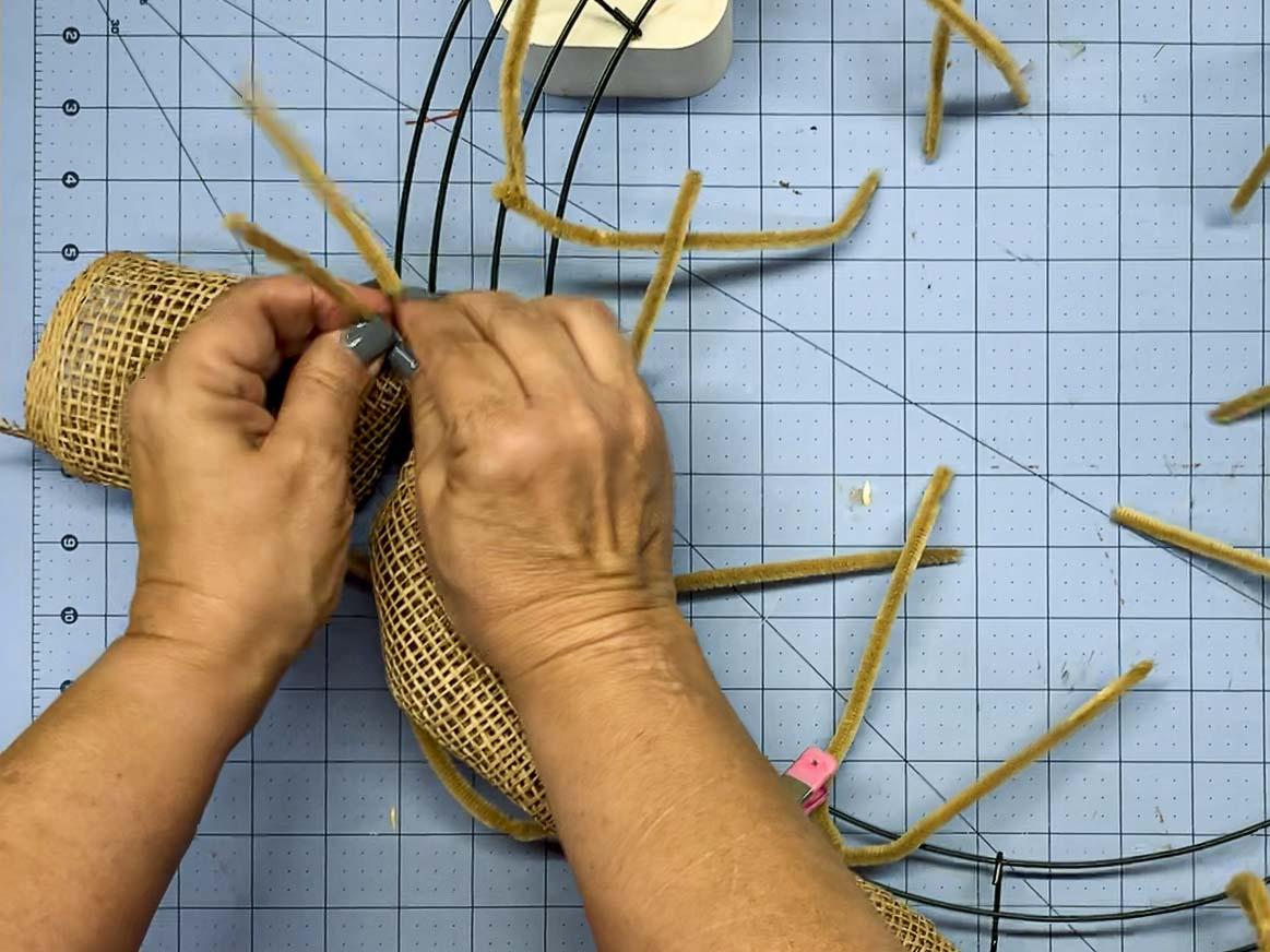 Hands attaching the first rolled piece of poly burlap mesh to the wire wreath form using pipe cleaners.