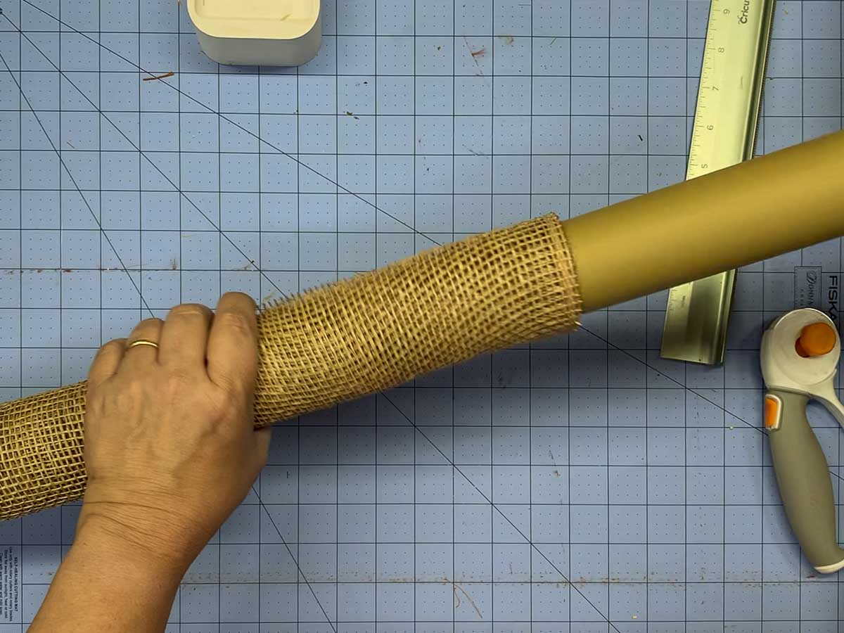 Removing a cardboard tube from a roll of poly burlap mesh.