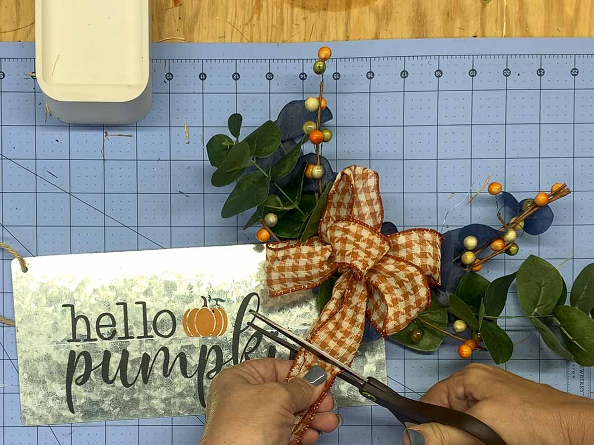Trimming ribbon tails on a bow for a wreath sign