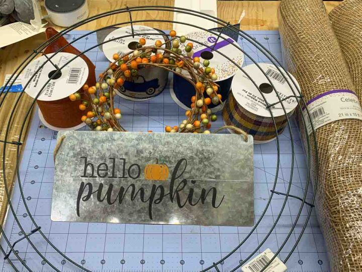 """Supplies for making a mesh pumpkin wreath, including an 18"""" wire wreath form, 2 rolls of 21"""" poly burlap mesh, 2.5"""" wired ribbon (4 complementary styles), a Hello Pumpkin wreath sign, and a fall berry garland."""